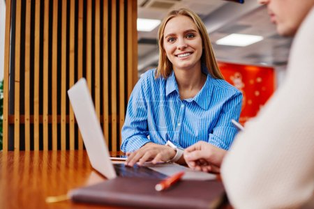 Photo for Portrait of charming positive hipster girl dressed in casual wear smiling at camera while sitting at laptop computer and searching information on website using wireless internet connection - Royalty Free Image