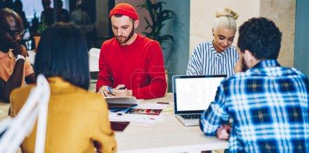 Photo pour Les recruteurs masculins et féminins du millénaire assis dans une bibliothèque moderne se sont concentrés sur l'apprentissage, une équipe multiraciale sérieuse d'employés s'interrogeant sur les moyens d'accroître les revenus de l'entreprise sur le tabl de réunion - image libre de droit