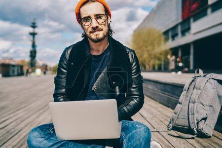 Photo pour Portrait d'étudiants de sexe masculin dans des lunettes pour fournir une protection des yeux assis avec ordinateur portable pour le réseautage et l'apprentissage en ligne, hipster type avec netbook connecté à l'internet 4G regarder la caméra - image libre de droit