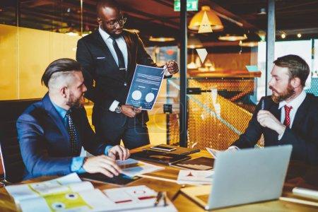 """Photo pour Une équipe diversifiée de professionnels discutant du rapport financier. Les membres de l """"équipe discutent du rapport financier. - image libre de droit"""