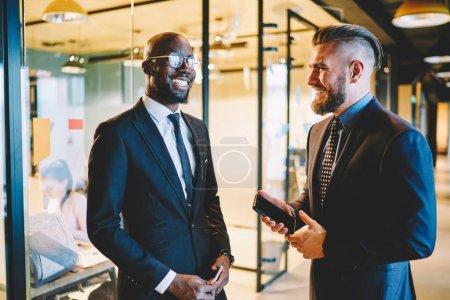 """Photo pour Deux partenaires d'affaires multiculturels en costume d """"époque se sont amusés lors d'une réunion dans le couloir. Les hommes entrepreneurs qui réussissent rient en parlant entre eux. Chers collègues présents à la réunion - image libre de droit"""