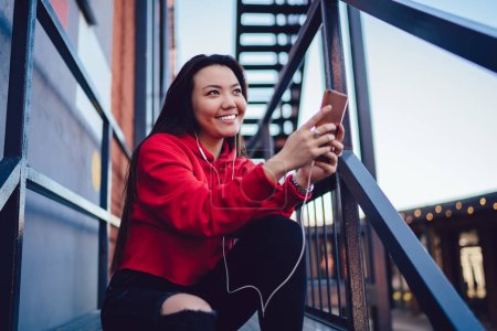 Photo for Happy japanese hipster girl listening positive audio message from friend during online chatting via smartphone application, cheerful asian millennial enjoying from using modern technology outdoors - Royalty Free Image