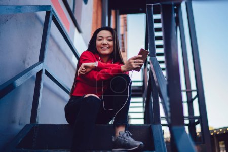 Photo for Portrait of cheerful japanese hipster girl dressed in casual wear listening audio music in modern earphones from playlist downloaded on smartphone device via public 4G internet, concept of generation - Royalty Free Image