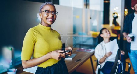 Photo for Cheerful african american female employee satisfied with job and occupation standing in coworking office with mobile phone, happy dark skinned business woman using smartphone and wifi during wor - Royalty Free Image