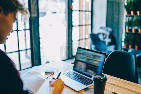 """Photo pour Vue croustillante de l """"étudiant Hipster écrivant de l'information pendant qu'il regarde le webinaire sur un ordinateur portable moderne avec connexion Internet sans fil. Jeune pigiste travaillant à distance sur le netbook. - image libre de droit"""