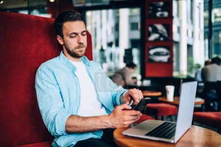 Photo for Serious skilled man in casual wear updating notification and screen settings on cellphone while working remotely with laptop device at public cafeteria, concept of technology and messaging - Royalty Free Image