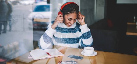 Photo for Happy african meloman enjoying favourite positive music playlist via bluetooth headphones sitting with textbook for writing during coffee break, cheerful woman feeling excited from listening radio - Royalty Free Image