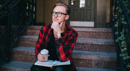 Photo pour Beau gars intelligent vêtu de vêtements et de lunettes à la mode se frottant le menton et regardant ailleurs avec un visage réfléchi tout en sirotant une boisson chaude et en prenant des notes dans un cahier de notes - image libre de droit