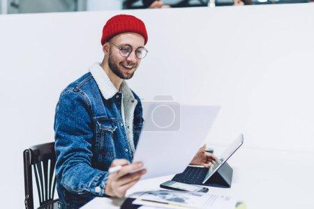 Photo pour Professionnel indépendant de l'habillement à la mode et des lunettes optiques pour protéger les yeux en souriant tout en travaillant dans un espace commun pour comptabiliser et vérifier l'information contenue dans le rapport - image libre de droit