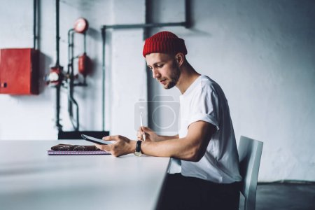 Photo for Side view of Caucasian male in trendy outfit sitting at office desktop and using modern cellphone gadget for checking information while working with project, millennial man typing text message - Royalty Free Image