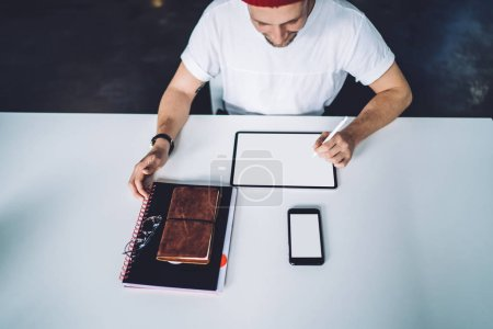 Photo for Top view of millennial hipster guy sitting at desktop with blank tablet with copy space area for art advertising and using electronic pen for drawing sketch, modern technology with mock up screens - Royalty Free Image