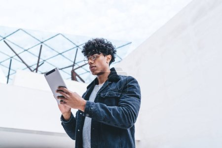 Photo for Millennial hipster guy in optical spectacles for vision correction typing content text for sharing publication while networking website with touch pad, young man checking online account balance - Royalty Free Image