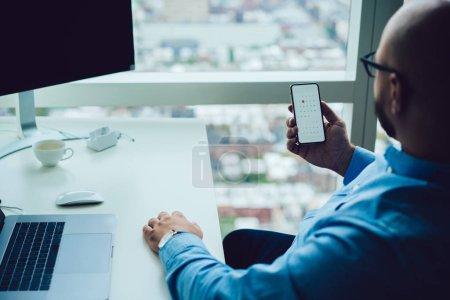 Photo pour Vue de dos de l'homme moderne en lunettes assis au bureau avec ordinateur portable et ordinateur et utilisant l'application de calendrier sur le smartphone - image libre de droit