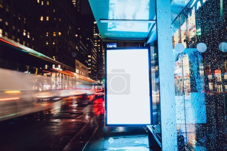 Photo for Bus station billboard in rainy night with blank copy space screen for advertising or promotional content, empty mock up Lightbox for information, blank display in urban city street with long exposure - Royalty Free Image