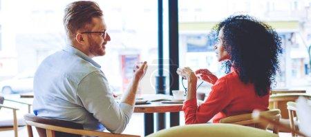 Foto de Asociación de gestores multiculturales inteligentes de la cafetería, retrospectiva de los administradores masculinos y femeninos serios se comunican durante la reunión de negocios en el área de publicidad pensando en soluciones - Imagen libre de derechos