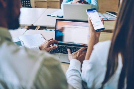 Rückansicht der weiblichen Hand mit Smartphone-Gadget im Chat mit einem Freund über mobile Anwendung in der Nähe eines männlichen Kollegen mit kostenloser drahtloser Verbindung auf einem Laptop-Gerät zum Herunterladen von Dateien online