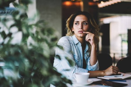 Photo for Thoughtful puzzled female student pondering on information for university course work, contemplative woman looking away while sitting at cafeteria table with textbook for education and smartphone - Royalty Free Image