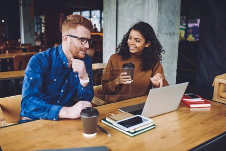 Photo for Positive male and female bloggers enjoying friendly meeting for discussing ideas for nest content publications on web page, happy diversity man and woman talking about new movie during coffee break - Royalty Free Image