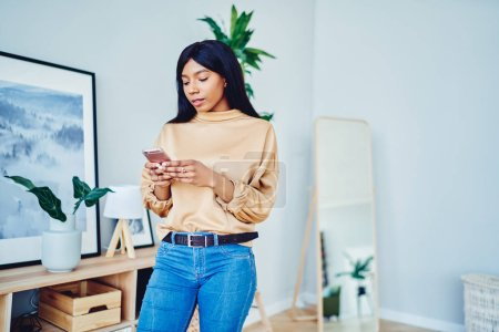 Photo for Pensive African American hipster girl in casual wear using mobile phone standing in living room, serious dark skinned female checking notification about message on smartphone at home interior - Royalty Free Image