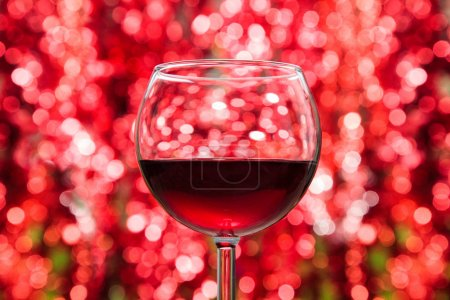 Photo for Two glasses of red wine against defocused holiday lights background. - Royalty Free Image
