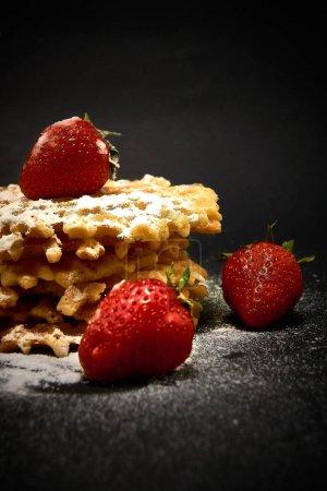 Photo pour Gaufres sucrées croustillantes aux fraises fraîches, sur fond sombre - image libre de droit