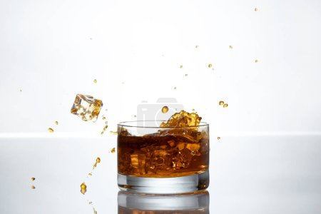 Photo for An Ice cube splashes into a glass of whisky - Royalty Free Image