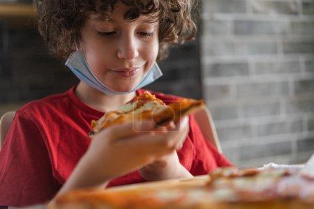 Photo pour Garçon mangeant de la pizza dans un restaurant pendant une pandémie de coronavirus. Réouverture des activités de restauration après le verrouillage. - image libre de droit