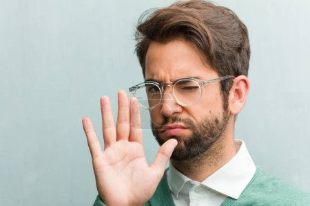 Photo pour Homme jeune entrepreneur beau visage closeup sérieuse et déterminée, mettre la main à l'avant, arrêter le geste, nier la notion - image libre de droit