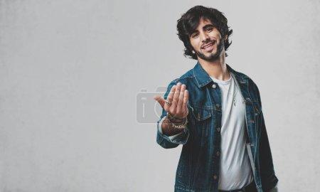 Photo pour Jeune bel homme invitant à venir, confiant et souriant faire un geste avec la main, être positif et amical - image libre de droit