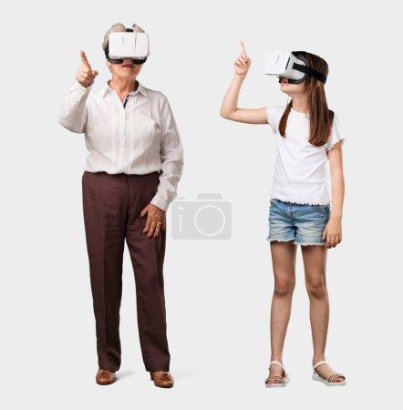 Photo pour Corps complet d'une dame âgée et de sa petite-fille excités et divertis, jouant avec des lunettes de réalité virtuelle, explorant un monde imaginaire, essayant de toucher quelque chose - image libre de droit