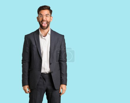 Photo for Young handsome business man funnny and friendly showing tongue - Royalty Free Image