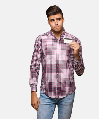 Young man holding credit card thinking about an idea