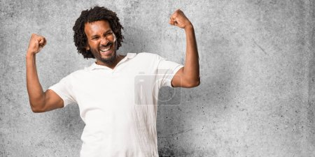 Photo for Handsome african american very happy and excited, raising arms, celebrating a victory or success, winning the lottery - Royalty Free Image