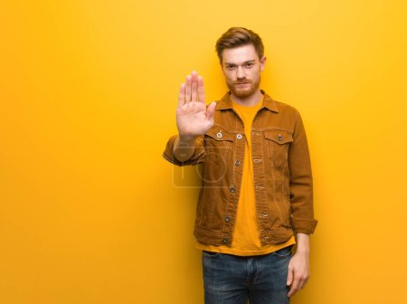 Photo for Young redhead man putting hand in front - Royalty Free Image