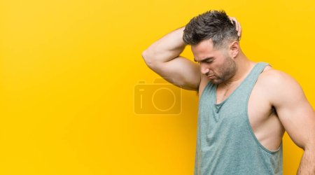 Photo for Young fitness man against a yellow background touching back of head, thinking and making a choice. - Royalty Free Image