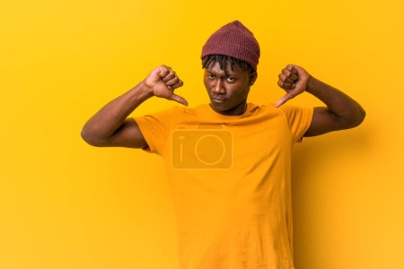 Young black man wearing rastas over yellow background feels proud and self confident, example to follow.