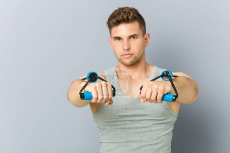 Photo for Young fitness caucasian man practicing with an elastic band. - Royalty Free Image