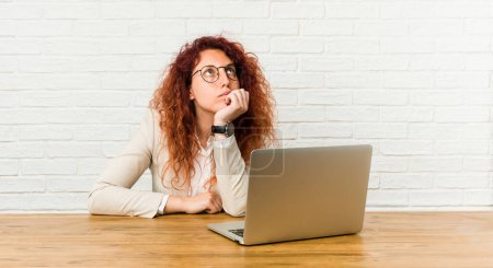 Photo for Young redhead curly woman working with her laptop looking sideways with doubtful and skeptical expression. - Royalty Free Image
