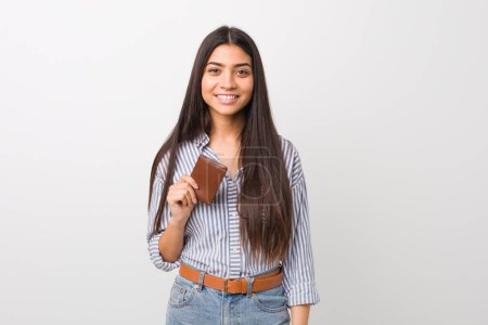 Photo for Young arab woman holding a wallet happy, smiling and cheerful. - Royalty Free Image