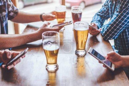 Photo pour Amis boire de la bière, surfer sur les smartphones et rire au bar - image libre de droit