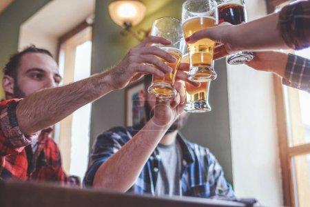 Photo pour Boire de la bière. Groupe d'amis dégustant une bière au pub, trinquant et riant. - image libre de droit