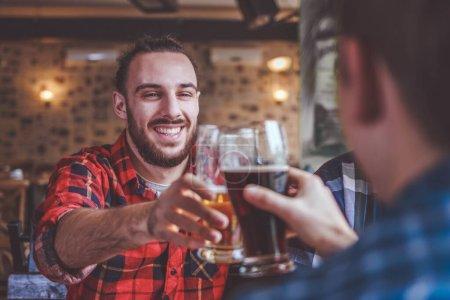 Photo pour Amis boire de la bière et des verres cliquetis au bar ou pub - image libre de droit
