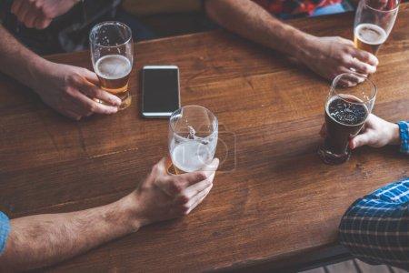 Photo pour Groupe d'amis dégustant une bière au pub, trinquant et riant. Fermer et se concentrer sur les lunettes. - image libre de droit