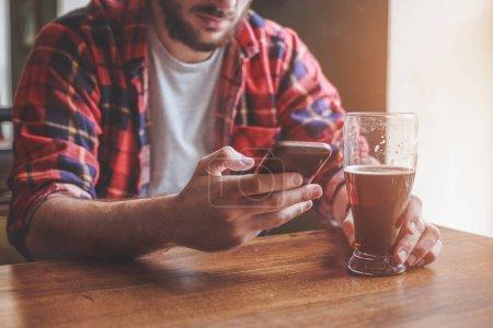 Photo pour Boire de la bière et utiliser un smartphone dans le bar. Gros plan - image libre de droit