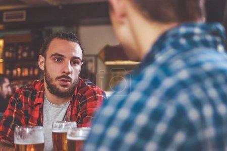 Photo pour Boire de la bière et parler au bar - image libre de droit