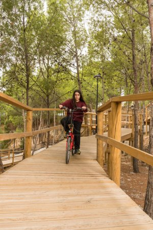 Photo for Vertical photograph of a teenager with long hair or a girl descending a wooden ramp with her folding bike surrounded by nature and trees. - Royalty Free Image