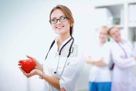 Médecin avec stéthoscope tenant coeur, isolé sur fond blanc