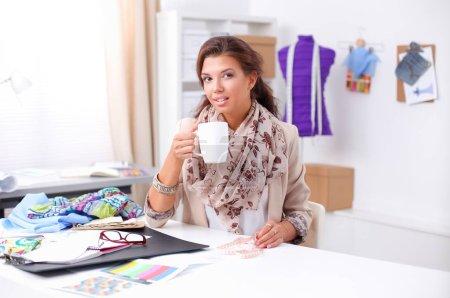 Young womamn fashion designer working at studio