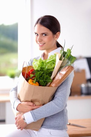 Young woman holding grocery shopping bag with vegetables . Standing in the kitchen