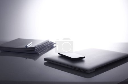 Photo for Laptop with stack of folders on table on white background. - Royalty Free Image